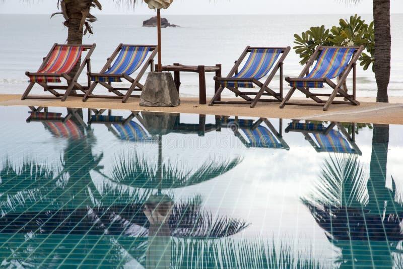 Basen i pokładu krzesło pod kokosowymi drzewkami palmowymi przy kurortem z pięknym dennym widokiem obraz royalty free
