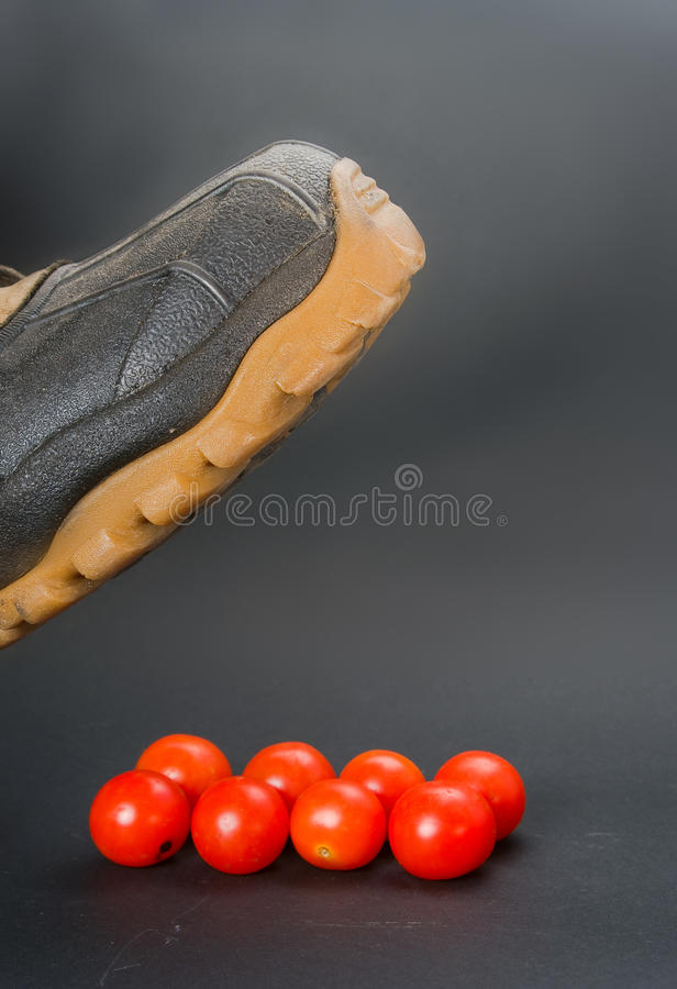 Baseness. The person is going to crush a boot small tomatoes royalty free stock images
