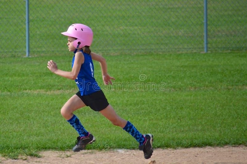 Bases corrientes de la chica joven en softball fotos de archivo libres de regalías