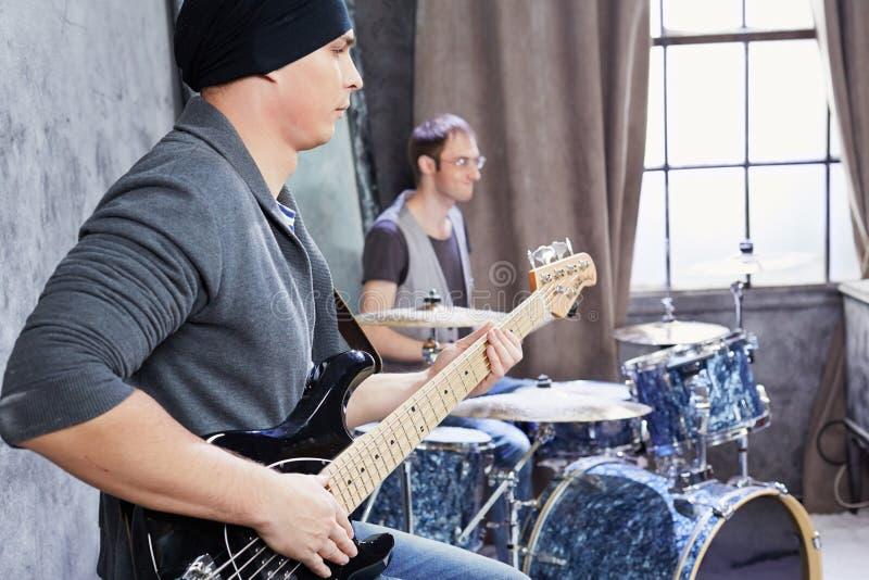 Basgitarist en slagwerkerspelmuziek royalty-vrije stock foto's