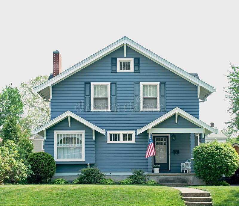 Basic Blue House with Small Porch. Basic, frame house in blue with white trim & blue shutters in Midwest with American flag royalty free stock photos