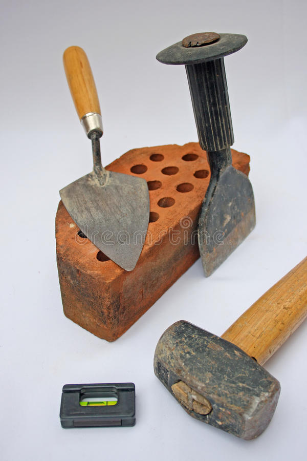 Basic building tools. Group of basic building tools. A hammer,bolster,trowel,spirit level and a brick stock image