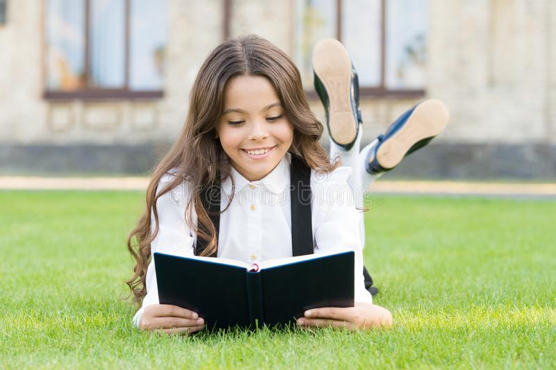 Basic education. Adorable little girl learn reading. Schoolgirl school uniform laying on lawn with favorite book. Studying concept. Extracurricular reading stock photos
