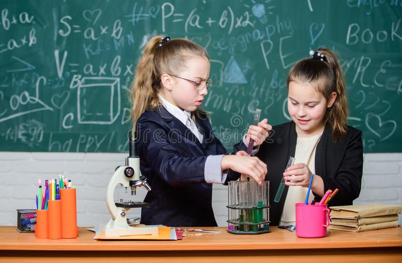Basic knowledge of chemistry. Pupils cute girls use test tubes with liquids. Chemical experiment concept. Safety stock images
