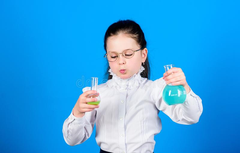 Basic knowledge. Knowledge day. Serious about studying. Schoolgirl with chemical liquids. Childhood and upbringing. Knowledge and information. Experimenting a stock photo