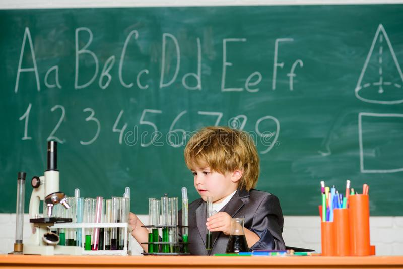 Basic knowledge primary school education. Educational experiment. Happy childhood. Boy near microscope and test tubes stock images