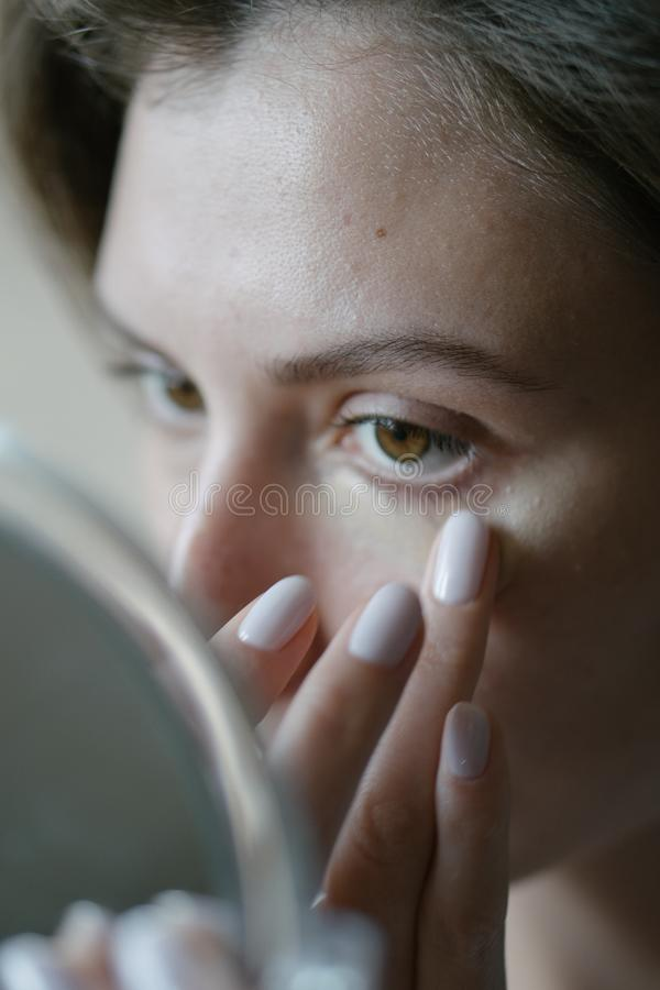 Basic make-up the morning before work. A young woman applies cosmetics and looks into the hand mirror. Close-up stock photos