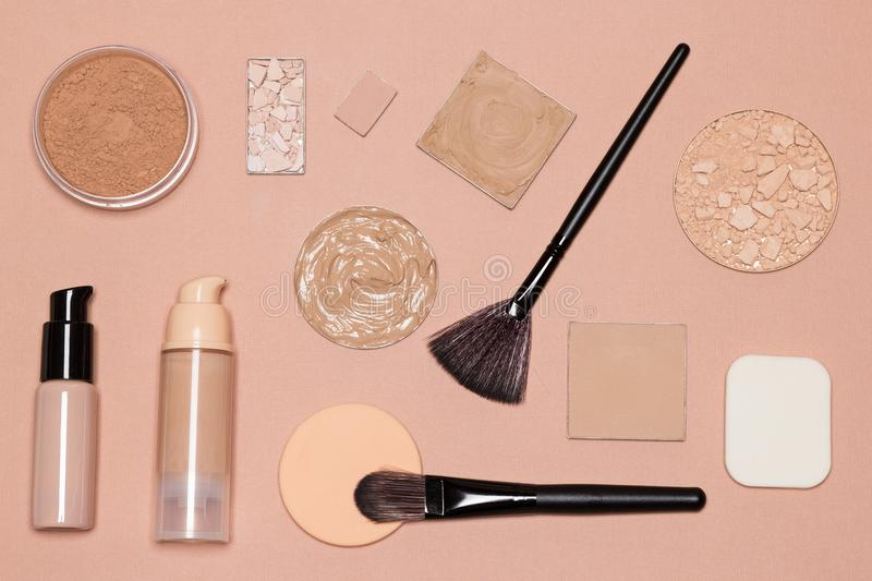 Basic makeup products to achieve even skin tone. And complexion: primer, foundation, cosmetic powders with make up brushes and sponges royalty free stock photos
