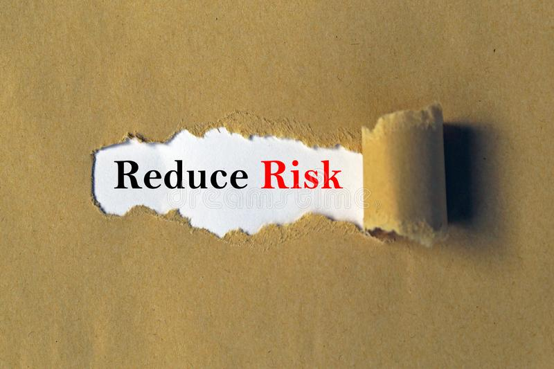 Reduce risk concept. 'Reduce Risk' in black and red print on a white background, visible beneath a section of brown textured paper that has been torn aside royalty free stock image