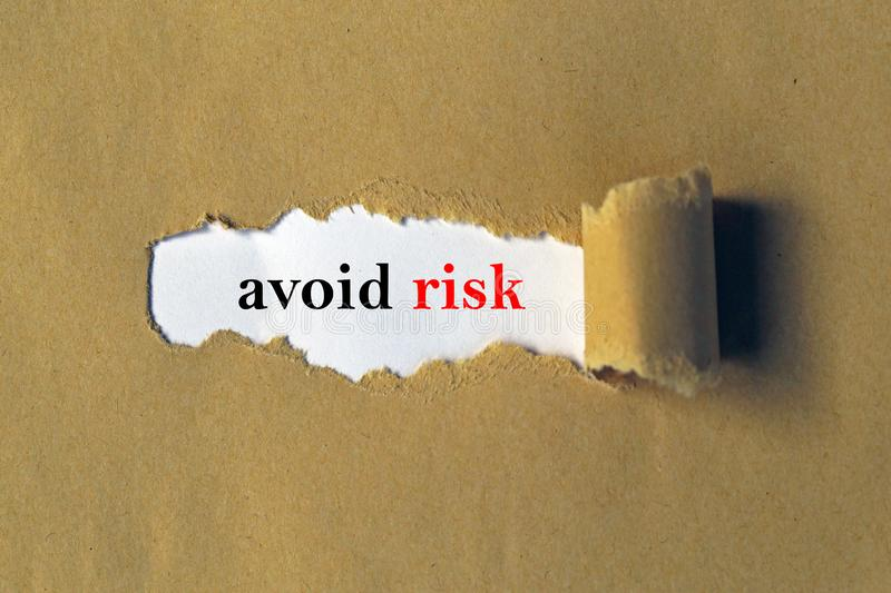 Avoid risk. Text 'avoid risk' in red and black lower case typescript on white paper viewed through a ragged slit in brown card stock photography