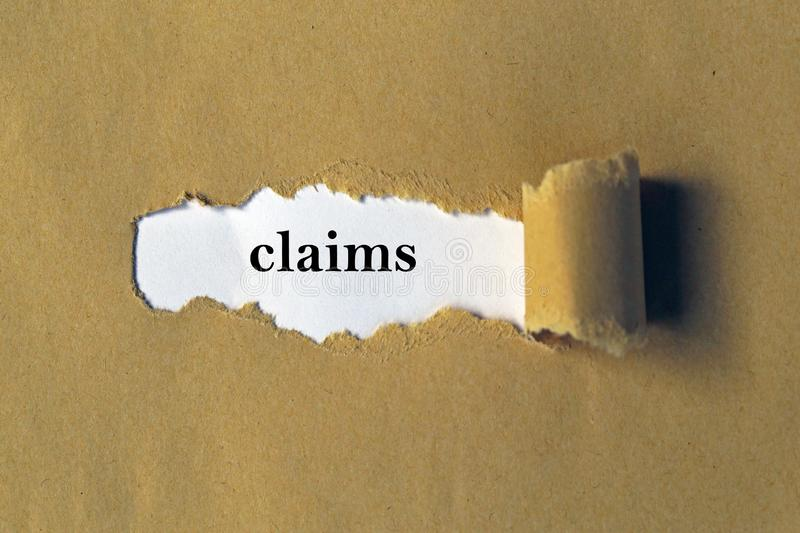 Claims heading. Behind torn brown paper royalty free stock image