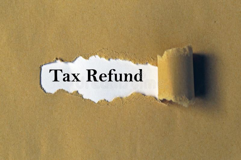 Tax Refund. A torn brown paper background revealing the word Tax Refund stock photography