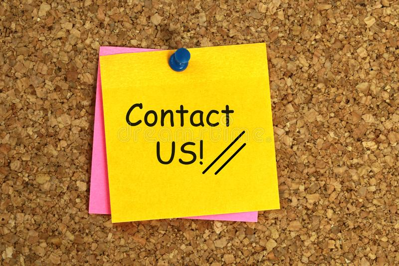 Contact us note. A yellow note pinned to a corkboard with the writing contact us stock photos