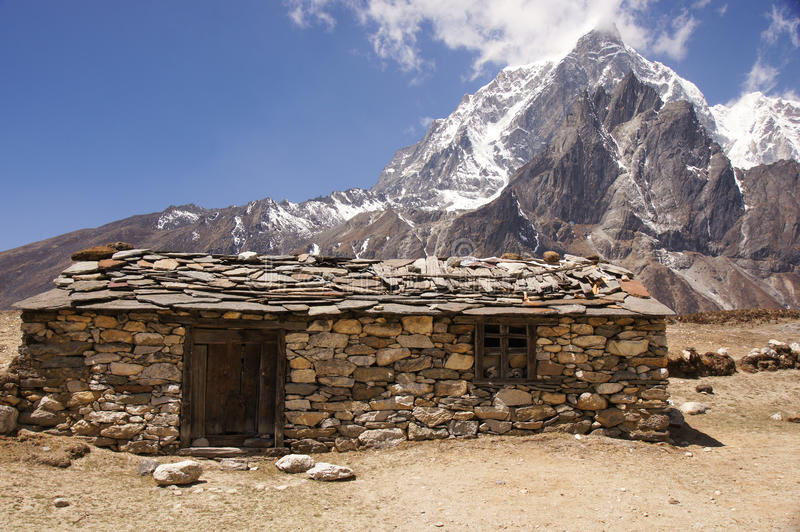 Basic stone cabin and mountain royalty free stock photos