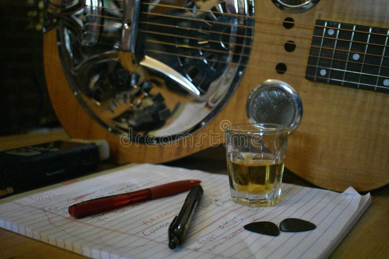 Songwriter Tools of the Trade 1. Basic tools of the trade for songwriter plus a whiskey shot for good measure. In the foreground, pens, guitar picks, and a shot royalty free stock photos