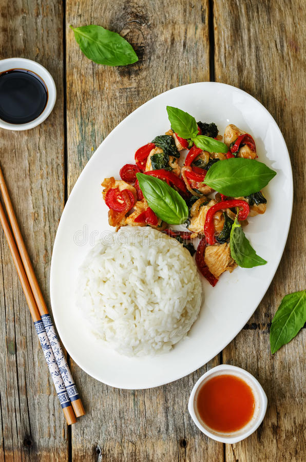 Basil pepper chicken stir fry with rice. The toning. selective focus royalty free stock photo