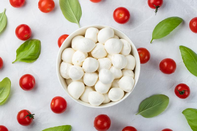 Basil, tomatoes and mozzarella in bowl for caprese salad, italian food and mediterranean diet concept on a light background. Top v royalty free stock photo