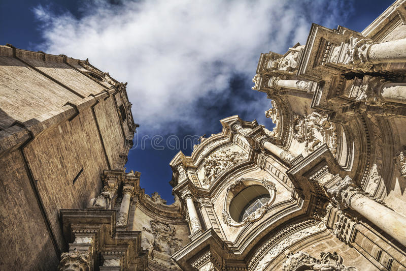 Basilica of the Assumption of Our Lady of Valencia, Spain. Dramatic scene with clouds and facade of Metropolitan Cathedral–Basilica of the Assumption of royalty free stock photos