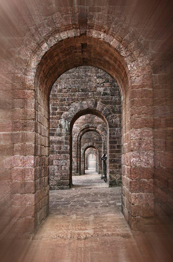 Basilica of Bom Jesus corridor. Basilica of Bom Jesus Church empty corridor with brick walls and arches in Panaji, Old Goa, India royalty free stock photography