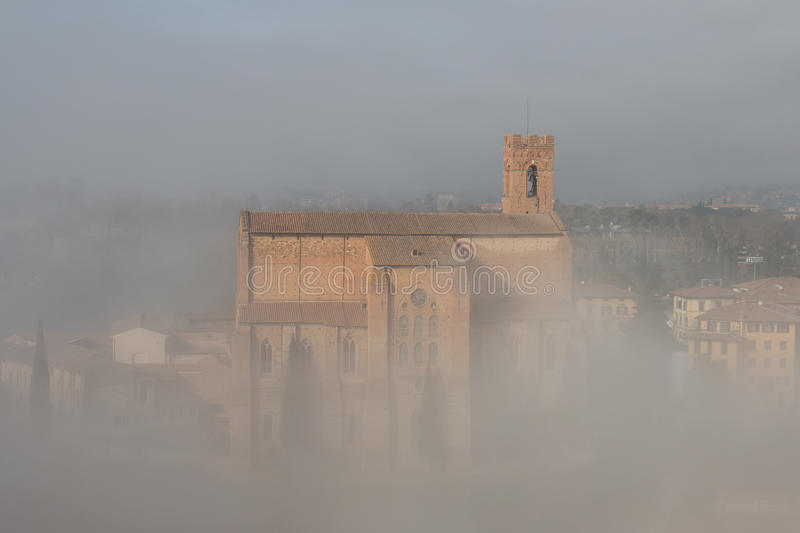 Basilica Cateriniana or Basilica of San Domenico in the thick fog, Siena, Tuscany, Italy. stock images