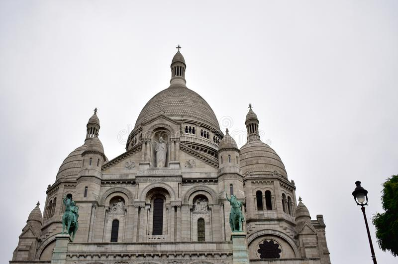 Basilica of the Sacred Heart Sacre Coeur. Paris, France, Facade with statues, dome and towers. Rainy day, grey sky. Basilique du Sacre Coeur, Montmartre. Paris royalty free stock image