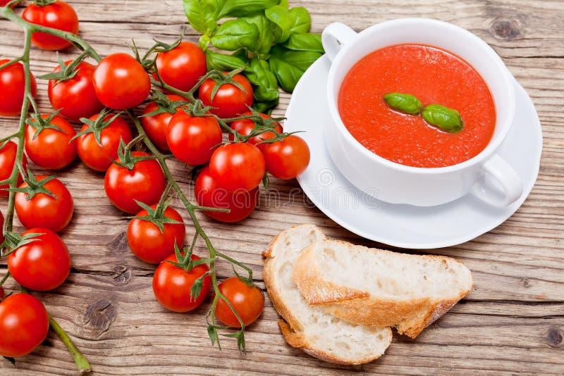 Basilico e pane freschi saporiti della minestra del pomodoro immagini stock