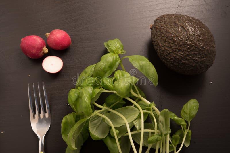 Basilicum, radijs, avocado en vork op zwarte achtergrond stock foto