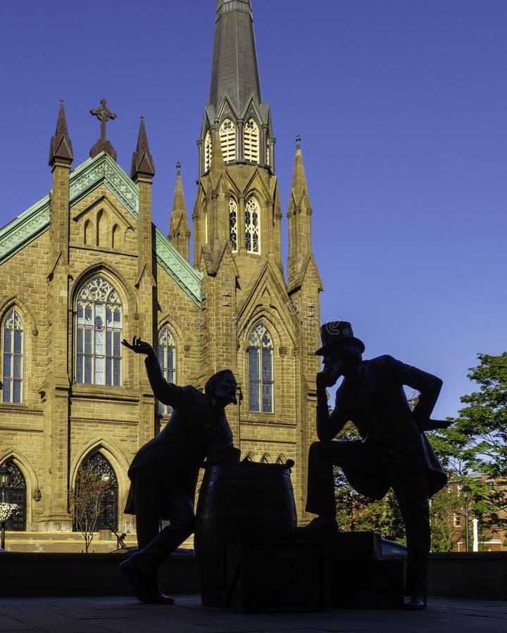 Basilika-Kathedrale St. Dunstans und die Bronzestatue von zwei Vätern Bündnis am schönen Morgen in Charlottetown lizenzfreies stockbild