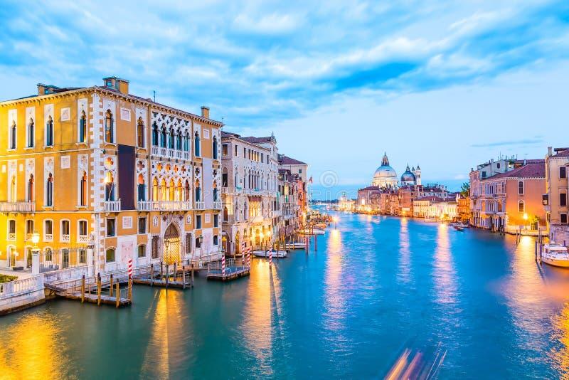 Basilika Santa Maria della Salute, Punta della Dogona och Grand Canal på den blåa timmesolnedgången i Venedig, Italien med fartyg royaltyfria foton