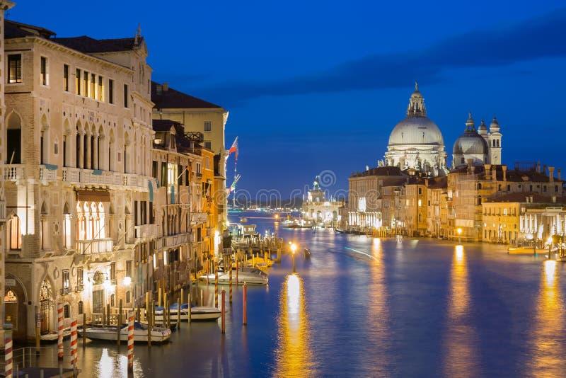 Basilika Santa Maria della Salute, Punta della Dogona och Grand Canal på den blåa timmesolnedgången i Venedig, Italien med reflex royaltyfri foto