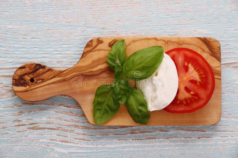 Basilikabladet, mozzarellaost och tomatskivan som Italien sjunker royaltyfri foto