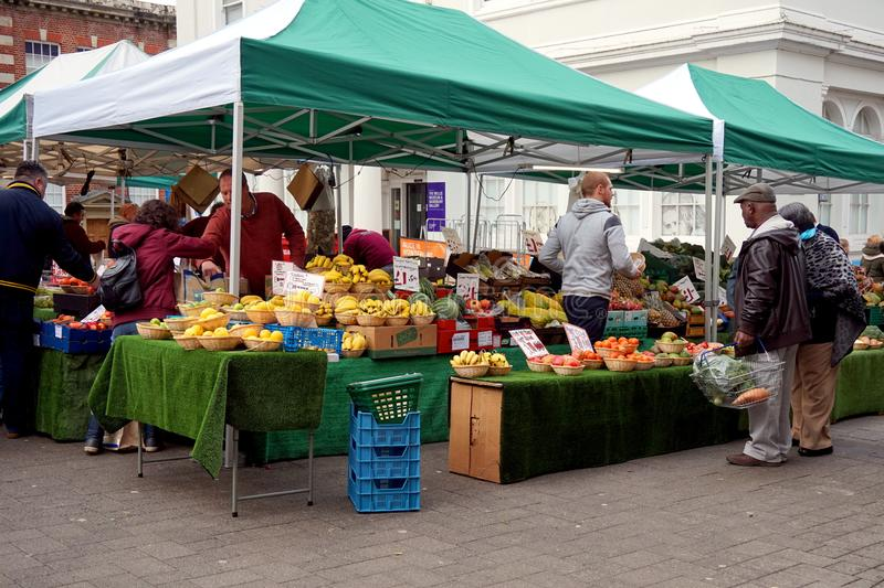 Basingstoke, UK - Jan 04 2016: Unidentified market traders and customers at a fruit stall in the Market Square in Basingstoke Hamp. Basingstoke, UK - Jan 04 2016 stock photo