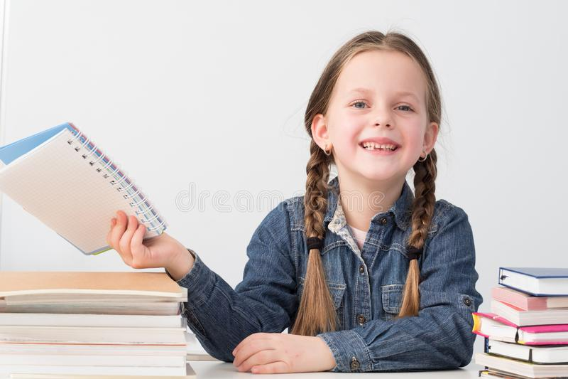 Basisonderwijs die de gelukkige boeken van het schoolmeisje glimlachen stock foto