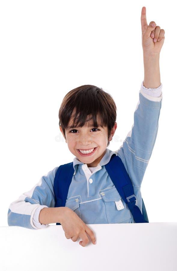 Basisschooljong geitje dat zijn hand opheft stock foto's