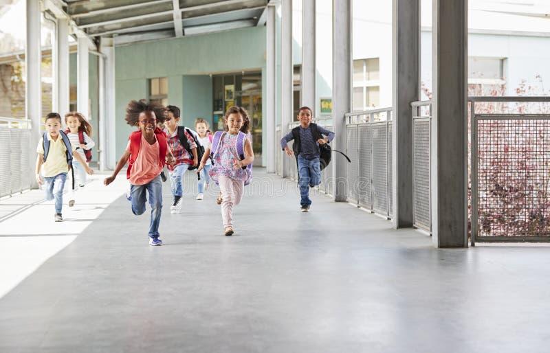 Basisschooljonge geitjes die aan camera in schoolgang lopen stock fotografie