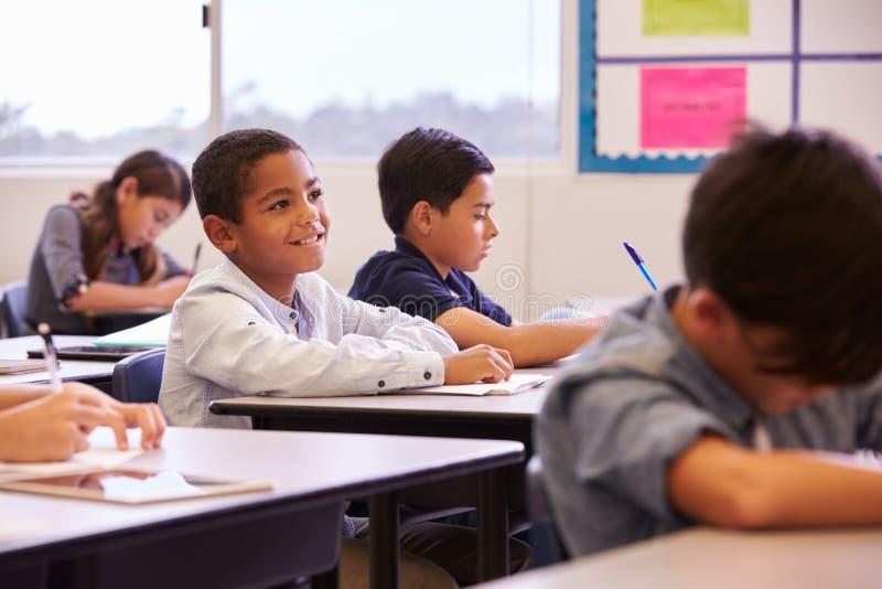 Basisschooljonge geitjes die bij hun bureaus in een klaslokaal werken royalty-vrije stock fotografie