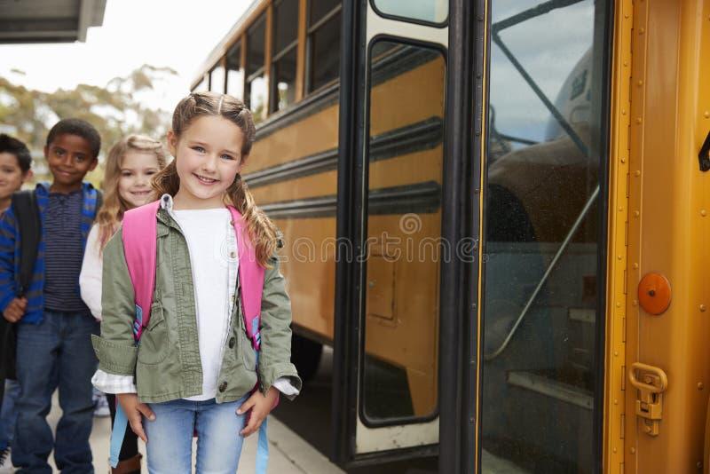 Basisschooljonge geitjes die de schoolbus wachten in te schepen stock foto