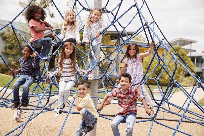 Basisschooljonge geitjes die in de schoolspeelplaats beklimmen stock fotografie