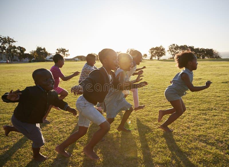 Basisschooljonge geitjes die samen op een open gebied lopen royalty-vrije stock afbeelding