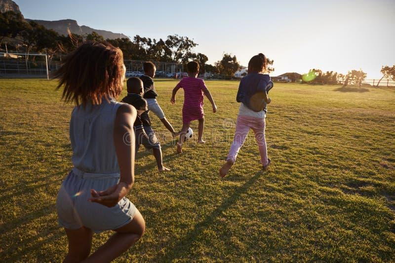 Basisschooljonge geitjes die voetbal op een gebied spelen, achtermening stock fotografie