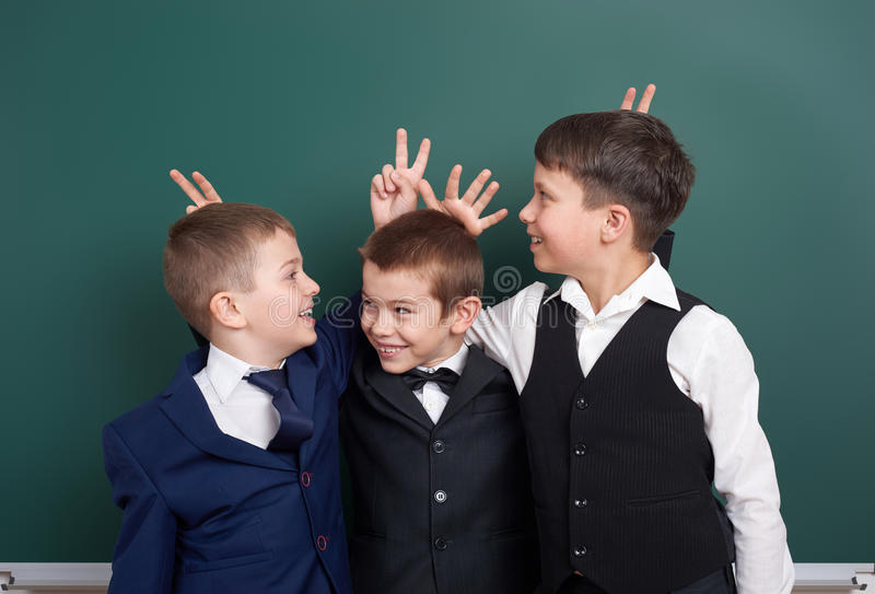 Basisschooljongen die rond dichtbijgelegen lege bordachtergrond voor de gek houden, gekleed in klassiek zwart kostuum, groepsleer stock afbeelding