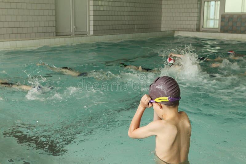 Basisschoolkinderen binnen het zwemmen vaardighedenles stock foto