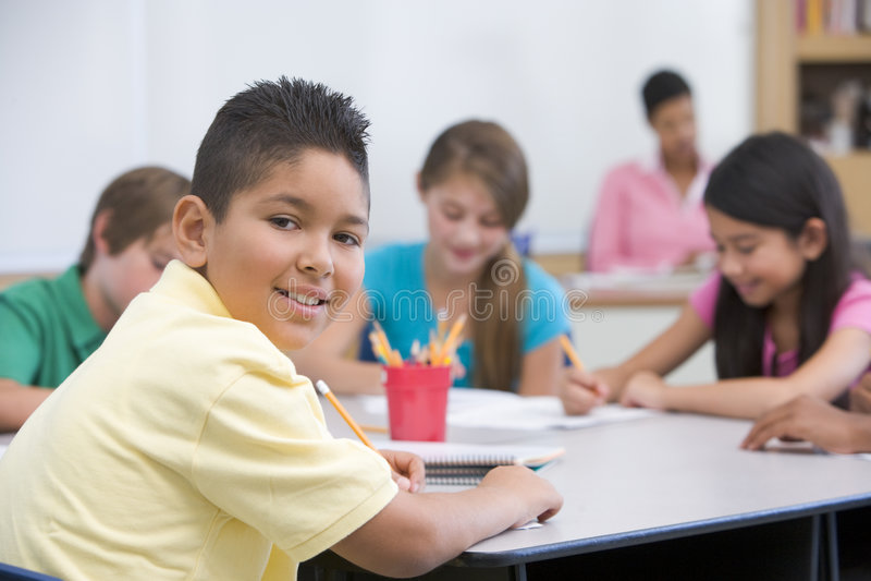 Basisschoolleerling in klaslokaal stock fotografie