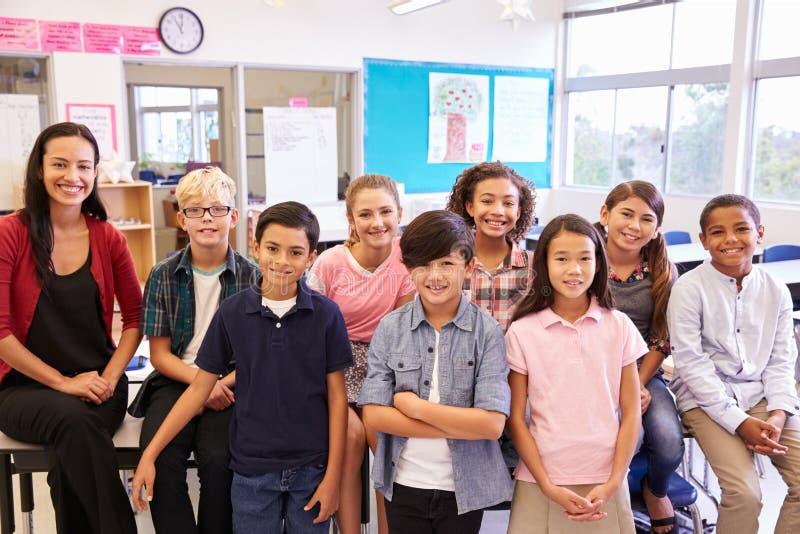 Basisschoolleraar en haar leerlingen in klaslokaal stock afbeelding