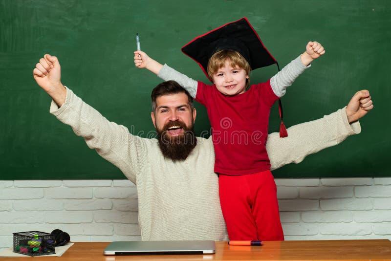 Basisschoolleraar en student in klaslokaal Yay ruim het glimlachen Woohoo Familiegeneratie Papa en zoon die hebben stock foto's