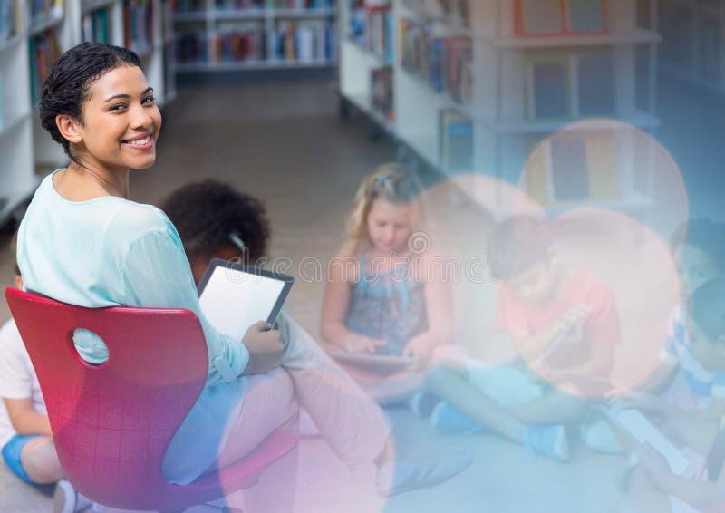 Basisschoolleraar met klasse in bibliotheek royalty-vrije stock afbeeldingen