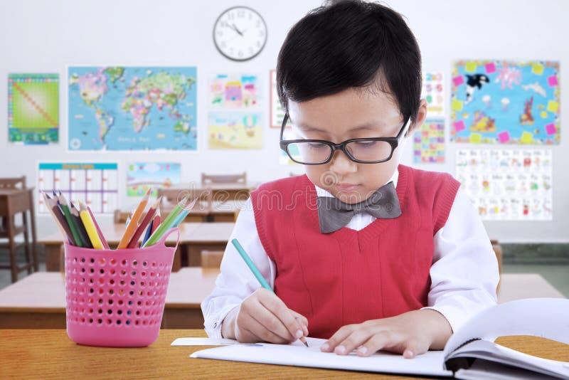Basisschoolstudent die op het document trekken stock afbeelding