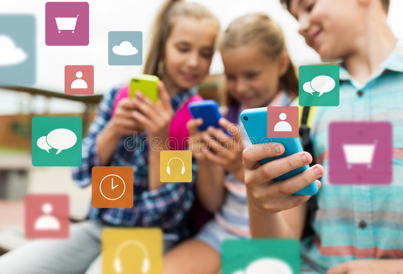Basisschoolstudenten met smartphones stock foto's
