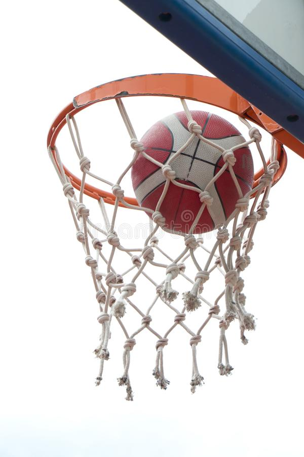 Basketball going through basket ring ant net. a successful clear point in low angle view stock image