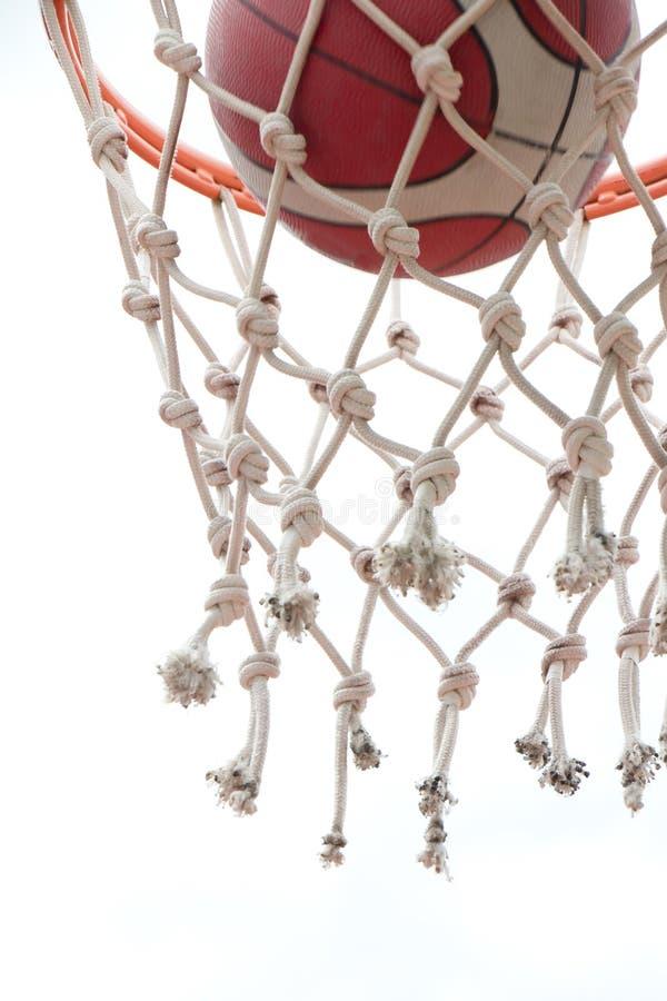 Baskeball som går till och med korgcirkelmyra, förtjänar en lyckad klar punkt i sikt för låg vinkel fotografering för bildbyråer